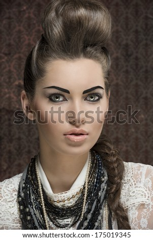 close-up shoot of fashion creative brunette girl posing with elegant hair-style and strong make-up,  white lace shirt and a lot of necklaces  - stock photo