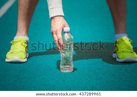 Close up shoot of male jogger hand holding plastic bottle of water on blue running track outdoors. Ideal for bottle pack shoot adding. Sport, fitness, nature and healthy lifestyle. - stock photo
