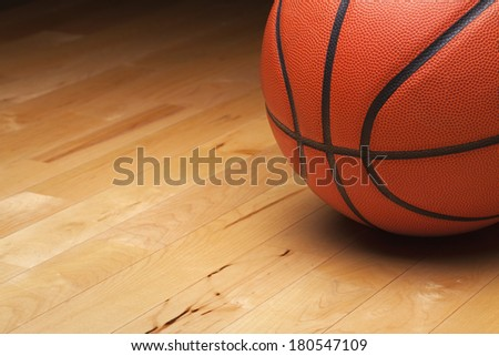 Close up shot of a basketball on a hardwood gym floor - stock photo