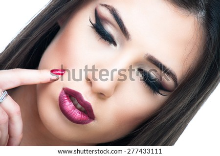 Close up shot of a beautiful brunette with closed eyes and finger on her face - stock photo