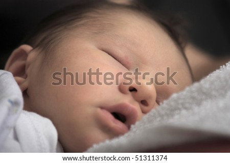 Close up shot of a beautiful new born baby sleeping peacefully - stock photo