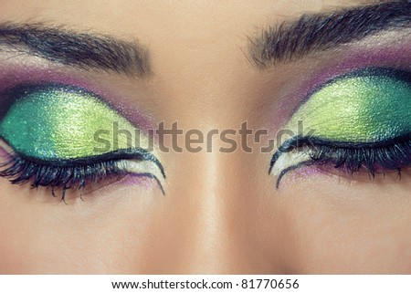 Close-up shot of a beautiful young woman's face with colorful eye make-up - stock photo