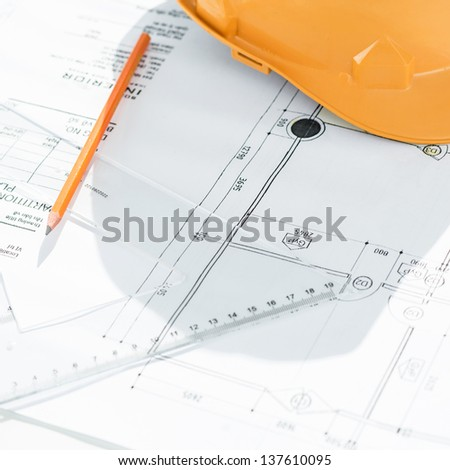 Close-up shot of a blueprint in detail with a pencil, ruler and hardhat