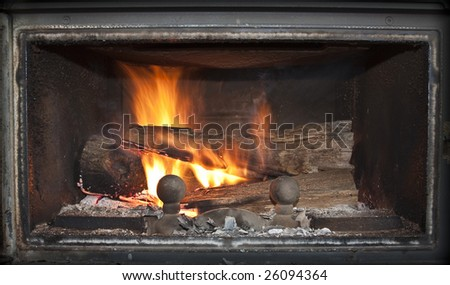 Close-up shot of a burning log in a fireplace.