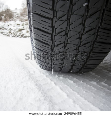 Close up shot of a car's tire in snow at winter - stock photo