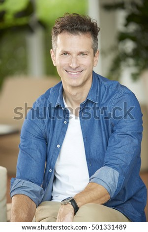 Close-up shot of a casual handsome man looking at camera and smiling while sitting on sofa.