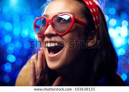 Close-up shot of a cheerful or surprised girl wearing heart-shaped sunglasses - stock photo