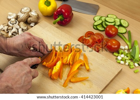 Close up shot of a chefs hands slicing a cleaned orange bell pepper on a wooden chopping board aside a selection of chopped mixed vegetables - stock photo