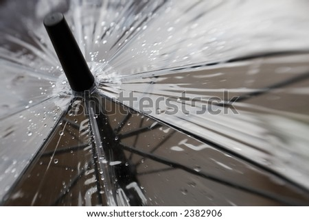 Close up shot of a clear umbrella with rain drops on it.  Image has a soft focus effect with just a small portion of the image sharp and the rest going out of focus. - stock photo