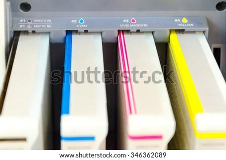 close-up shot of a CMYK ink cartridges for laser digital print copier machine - stock photo