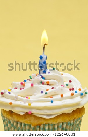 Close-up shot of a cupcake with sugar icing with burning candles over yellow background. - stock photo