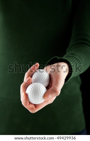 close up shot of a female hand holding two golf balls