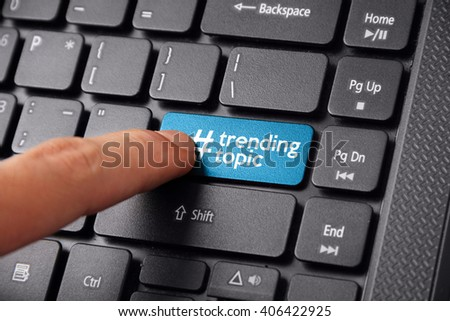 Close up shot of a finger clicking the TRENDING TOPIC button on a laptop keyboard - stock photo
