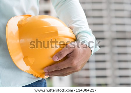 Close-up shot of a foreman holding a hardhat on the construction site