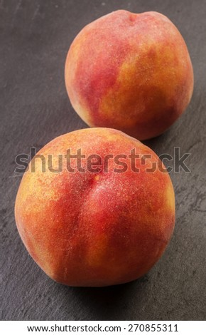 Close up shot of a fresh peach isolated on a black background - stock photo