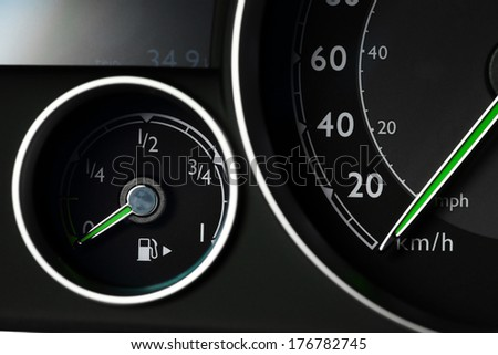 Close-up shot of a fuel gauge and a speedometer in a car - stock photo
