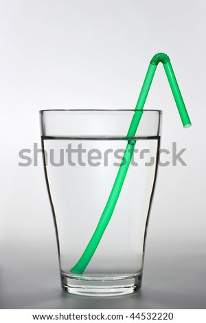 close up shot of a full water glass with a green drinking straw