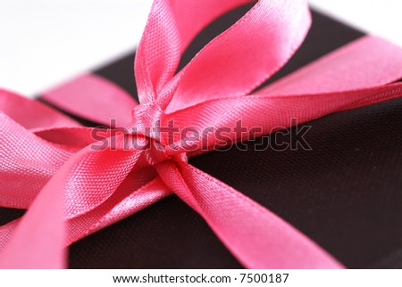 Close-up shot of a gift box with Pink ribbons. Shallow depth of field shot is intentional. - stock photo