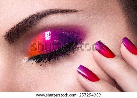 Close-up shot of a girl's eye with makeup and fingers with colorful manicure - stock photo
