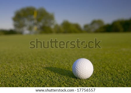 Close up shot of a golf ball on a green with an out of focus flag in the background.