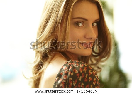 Close-up shot of a gorgeous beauty with curly hair and flirty look - stock photo