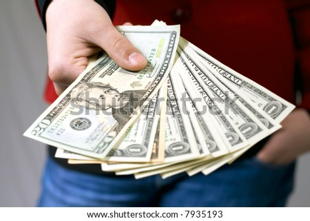 Close-up shot of a hand giving american dollars. Red modern dress and blue jeans. Studio shot.
