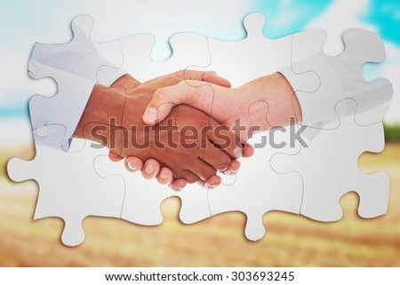 Close-up shot of a handshake in office against blue sky over fields