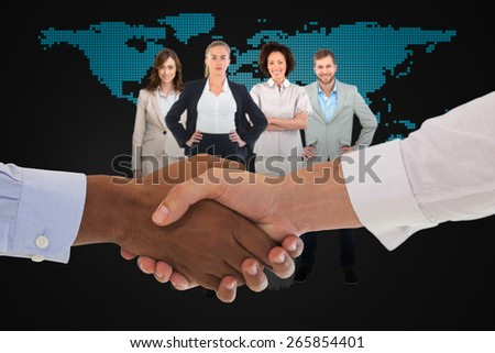 Close-up shot of a handshake in office against blue world map - stock photo