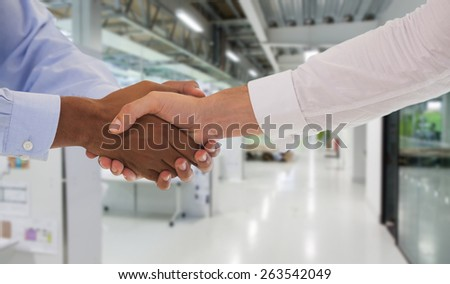 Close-up shot of a handshake in office against college hallway - stock photo