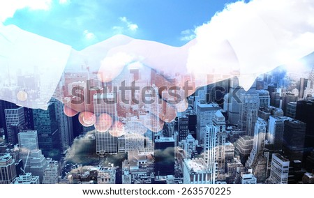 Close-up shot of a handshake in office against high angle view of city - stock photo