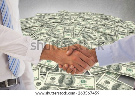 Close-up shot of a handshake in office against pile of dollars - stock photo
