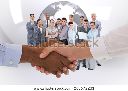 Close-up shot of a handshake in office against planet on grey abstract background - stock photo