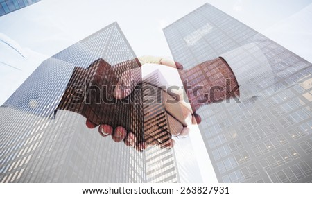 Close-up shot of a handshake in office against skyscraper - stock photo