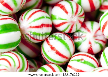 Close-up shot of a heap of colorful X-mas candies with green and red stripes. - stock photo