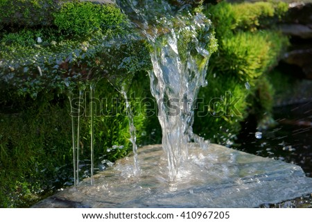 Close up shot of a homemade waterfall in a small backyard pond that filters water for a koi pond. - stock photo