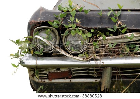 Close up shot of a junked car left in a field - stock photo