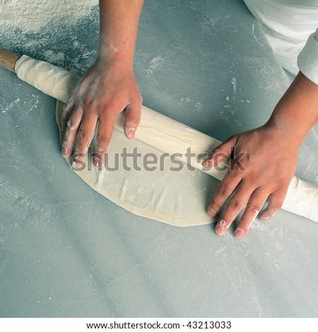 close up shot of a man rolling dough - stock photo