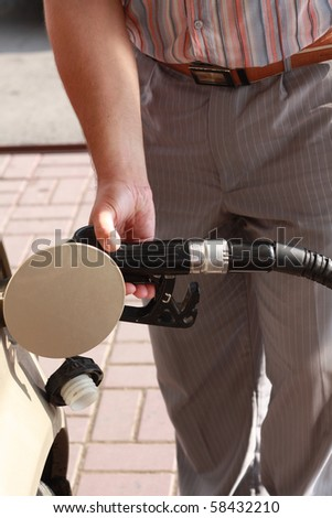 Close-up shot of a man's hand pumping gas - stock photo