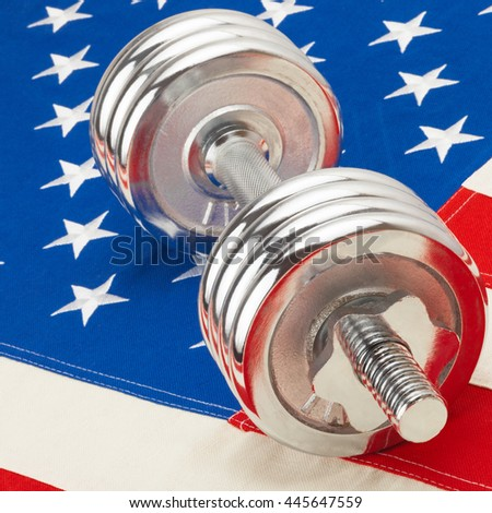 Close up shot of a metal dumbbell over USA flag as symbol of healthy life style - stock photo