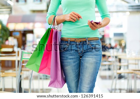 Close-up shot of a modern shopper with a mobile phone and colorful shopping bags - stock photo