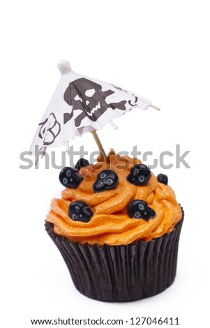 Close-up shot of a orange cupcake with skull topping and canopy with skull design isolated over white background. - stock photo