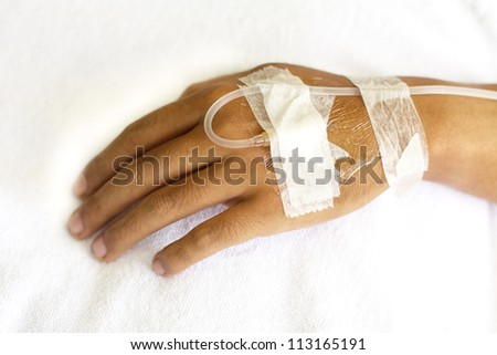 close up shot of a patient's hand with saline intravenous (iv)