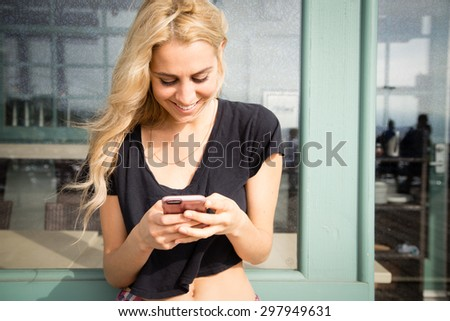 Close up shot of a pretty young woman texts on her mobile phone. She is smiling and happy, She looks like a California Beach girl. She is outside on a summer day on a boardwalk. - stock photo