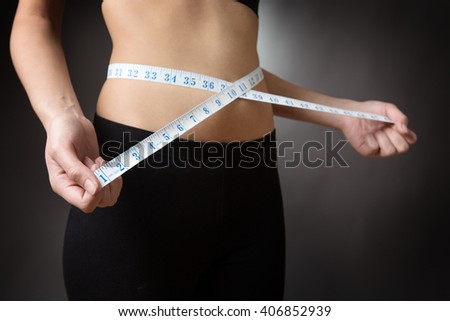 Close up shot of a slim models abdomen with a tape measure wrapped around. low key lighting shot on a grey background - stock photo