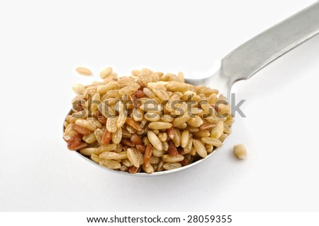 Close up shot of a spoon full of wholegrain rice with oats and pearl barley on white background