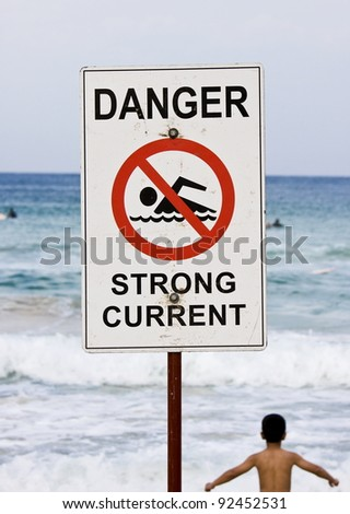 Close-up shot of a warning sign at a sea beach, shallow depth of field - stock photo