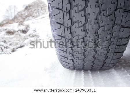 Close up shot of a wasted car tire in snow at winter - stock photo