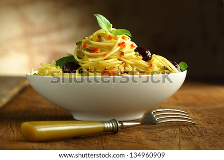 Close up shot of a white bowl filled with spaghetti pasta and olives and a fork. - stock photo