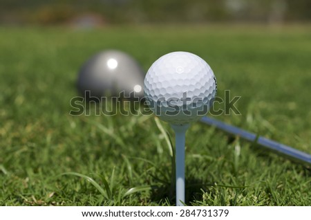 Close up shot of a white golf ball sitting on a tee. Long green grass around and out of focus golf club in background.