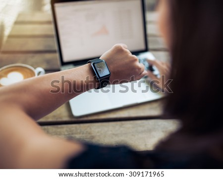 Close up shot of a woman checking time on her smartwatch. Female sitting in cafe with a laptop and cup of coffee. - stock photo